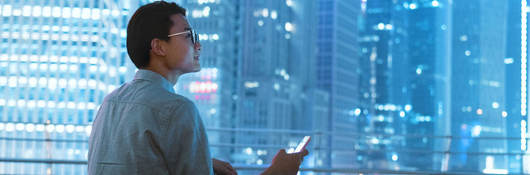 Man siting on roof of building holding smartphone