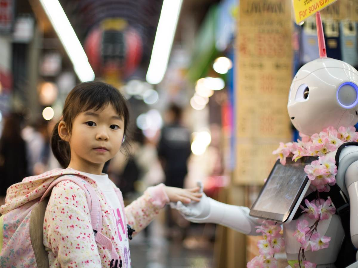 Kid holding hands with a robot