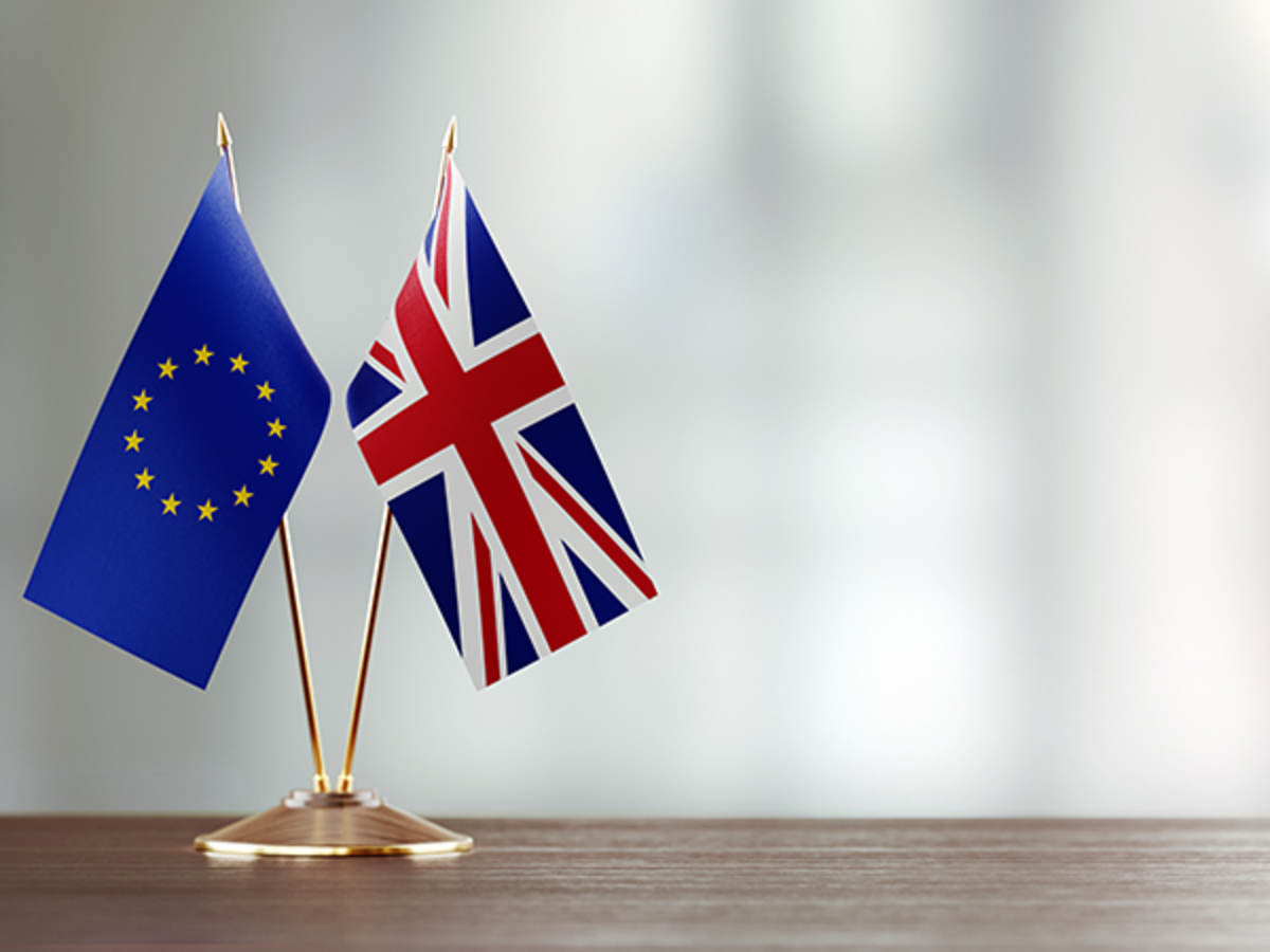 European-Union-And-British-Flag-Pair-On-A-Desk-Over-Defocused-Background