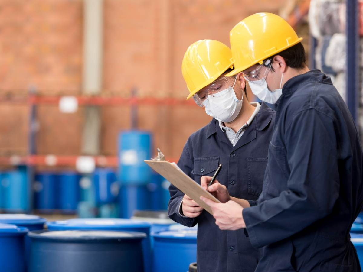 Two employees having a discussion and looking at a chart in a chemical plant